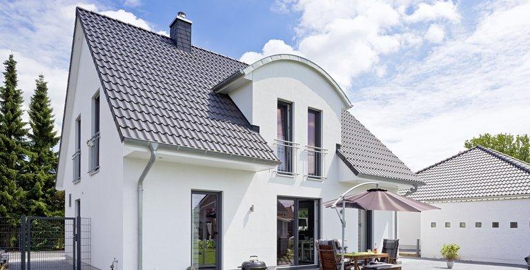 Die Bauherren haben sich für eine Tonnendachgaube an der Gartenseite ihres Satteldachhauses entschieden. Copyright: Heinz von Heiden GmbH Massivhäuser