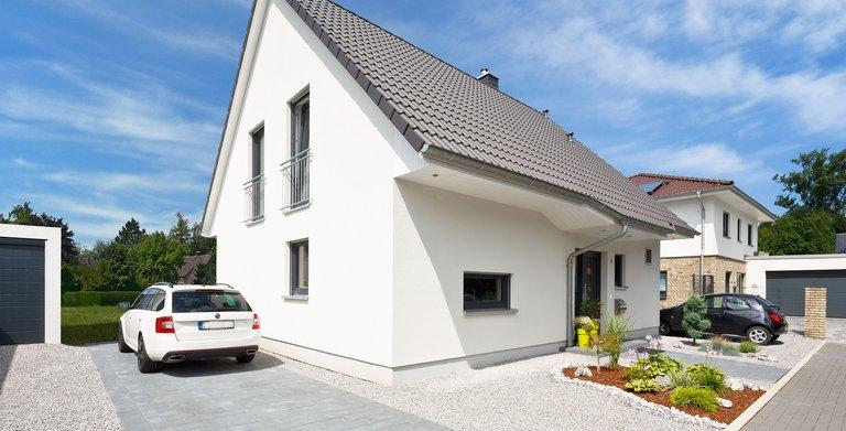 Weißer Putz, graue Fensterrahmen und Dachziegel – so präsentiert sich das massiv gebaute Einfamilienhaus.  Copyright: Heinz von Heiden GmbH Massivhäuser