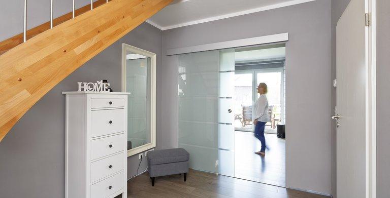 Die Diele wird durch eine Schiebe-Glastür vom Wohnbereich getrennt. Copyright: Heinz von Heiden GmbH Massivhäuser