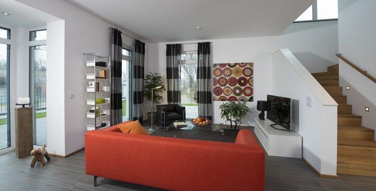 Der luftig gestaltete Wohnbereich mit dem voll verglasten Rechteck-Erker, dem offenen Treppenaufgang und der angeschlossenen Küche bildet den Lebensmittelpunkt des Hauses.